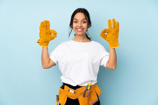 Giovane donna dell'elettricista sulla parete blu che mostra segno giusto con le dita
