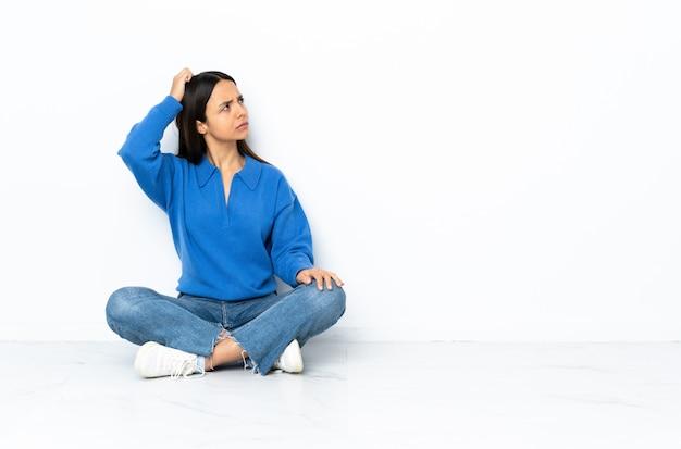 Giovane donna della corsa mista che si siede sul pavimento isolato su fondo bianco che ha dubbi mentre graffiando testa
