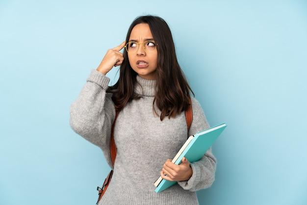 Giovane donna della corsa mista che va a scuola sulla parete blu che ha dubbi e pensare