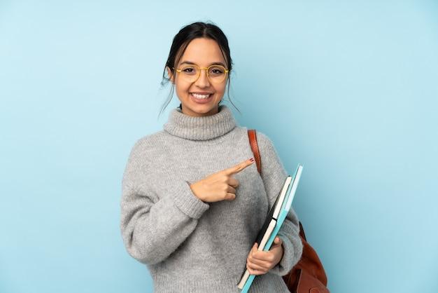Giovane donna della corsa mista che va a scuola sulla parete blu che indica il lato