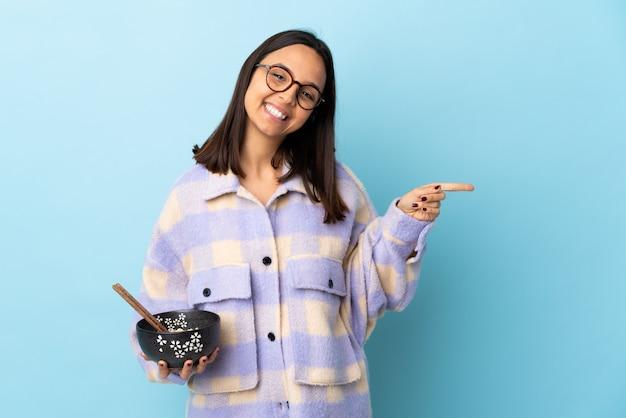 Giovane donna della corsa mista del brunette che giudica una ciotola piena di tagliatelle sopra la parete blu che indica barretta ai laterali e felice.