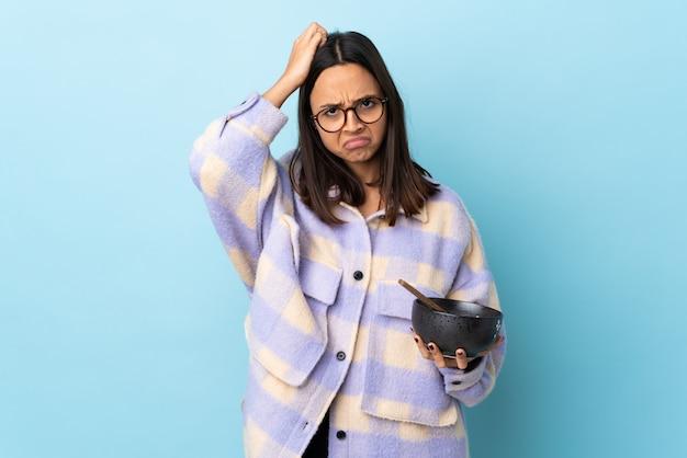 Giovane donna della corsa mista del brunette che giudica una ciotola piena di tagliatelle sopra la parete blu con un'espressione di frustrazione e di non comprensione
