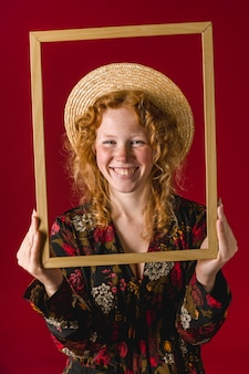 Giovane donna della testarossa che sorride e che tiene struttura di legno