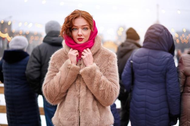 Giovane donna della testarossa che sta tempo di vacanza invernale
