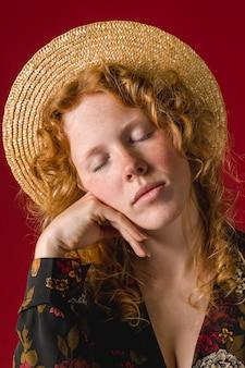 Giovane donna della testarossa con gli occhi chiusi che tengono mento