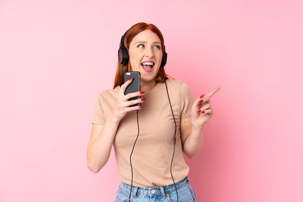 Giovane donna della testarossa sopra fondo rosa isolato facendo uso del cellulare con le cuffie e cantare