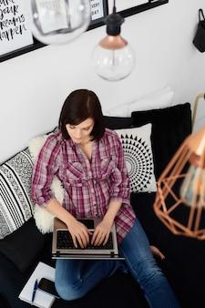 Giovane donna delle free lance che per mezzo del computer portatile.