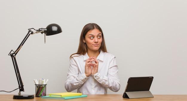 Giovane donna dello studente che lavora al suo scrittorio che elabora un piano