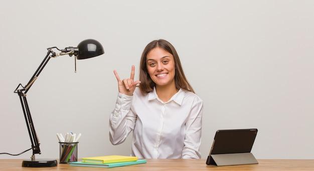 Giovane donna dello studente che lavora al suo scrittorio che fa un gesto della roccia