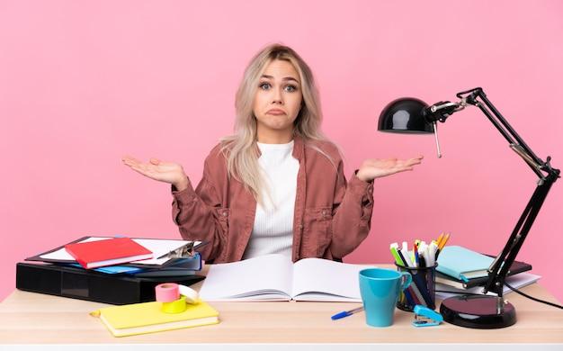 Giovane donna dello studente che lavora in una tabella che ha dubbi con l'espressione del viso confuso