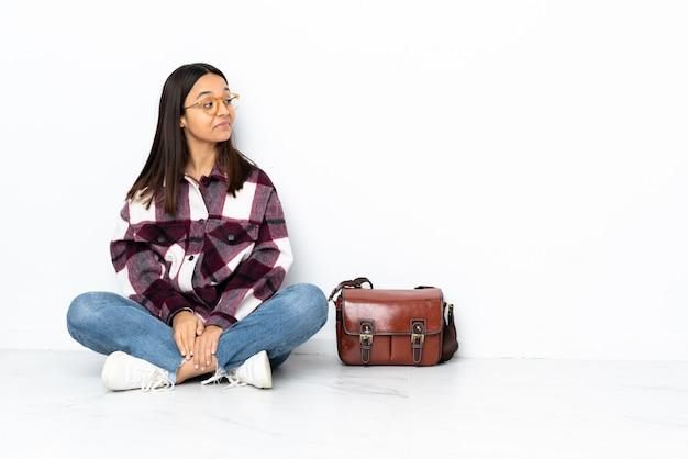 Giovane donna dello studente che si siede sul pavimento che ha dubbi mentre osservando lato