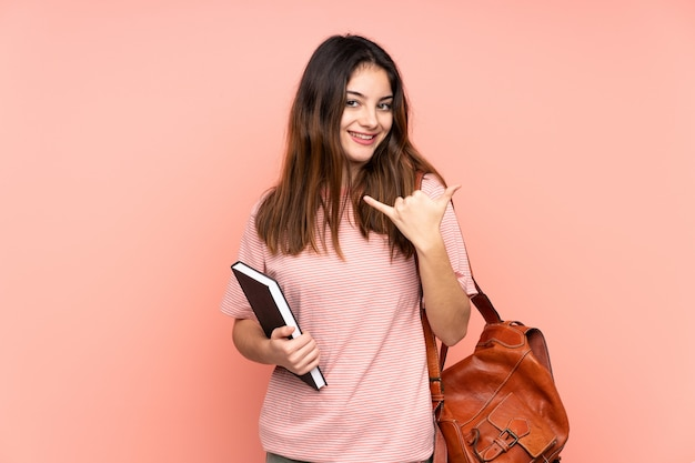 Giovane donna dello studente che va all'università sopra la parete rosa che grida con la bocca spalancata