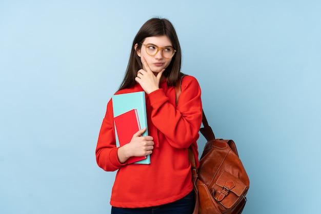 Giovane donna dello studente dell'adolescente che tiene un'insalata che pensa un'idea