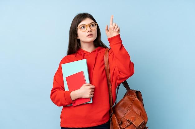 Giovane donna dello studente dell'adolescente che tiene un'insalata che tocca sullo schermo trasparente