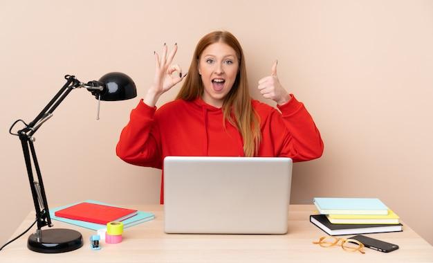 Giovane donna dello studente in un posto di lavoro con un computer portatile che mostra segno e pollice giusti sul gesto