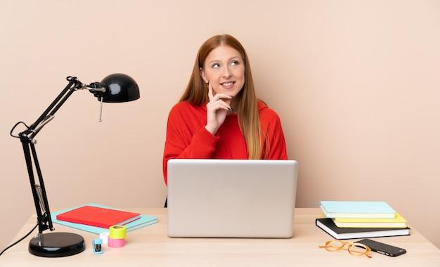 Giovane donna dello studente in un posto di lavoro con un computer portatile che pensa un'idea mentre guardando su