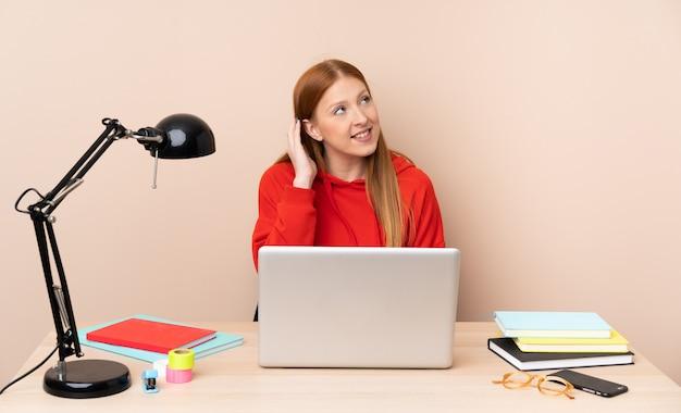 Giovane donna dello studente in un posto di lavoro con un computer portatile che pensa un'idea
