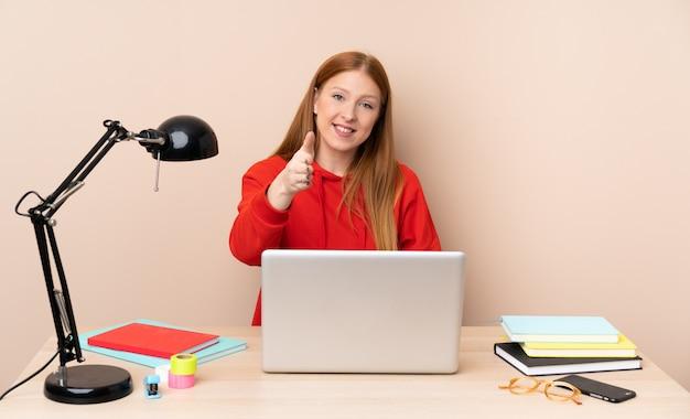 Giovane donna dello studente in un posto di lavoro con un computer portatile che stringe le mani per chiudere molto