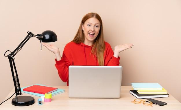 Giovane donna dello studente in un posto di lavoro con un computer portatile con espressione facciale colpita