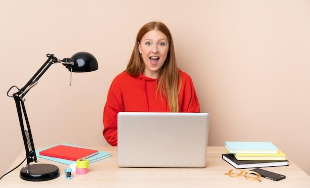 Giovane donna dello studente in un posto di lavoro con un computer portatile con espressione facciale di sorpresa