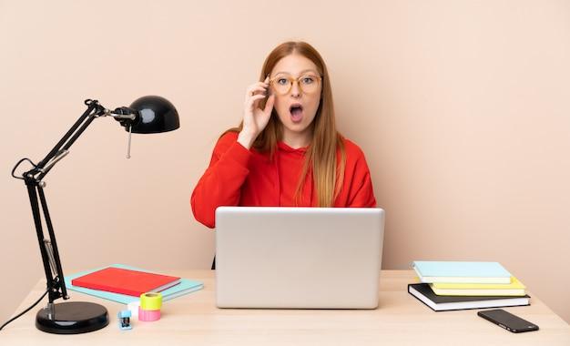 Giovane donna dello studente in un posto di lavoro con un computer portatile con gli occhiali e sorpreso