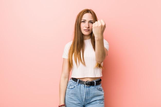Giovane donna dello zenzero di redhead contro una parete rosa che mostra pugno alla macchina fotografica, espressione facciale aggressiva