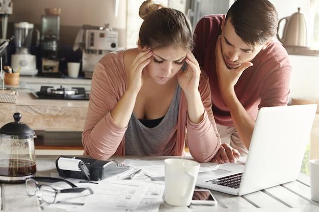 Giovane donna depressa che ha un forte mal di testa tenendo le tempie stressate dalla mancanza di soldi per pagare i debiti familiari, il marito perplesso in piedi accanto a lei, cercando di trovare una soluzione