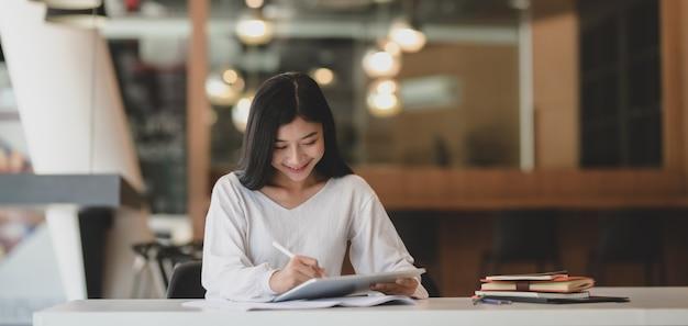 Giovane donna di affari adorabile che lavora al suo progetto mentre per mezzo della compressa digitale