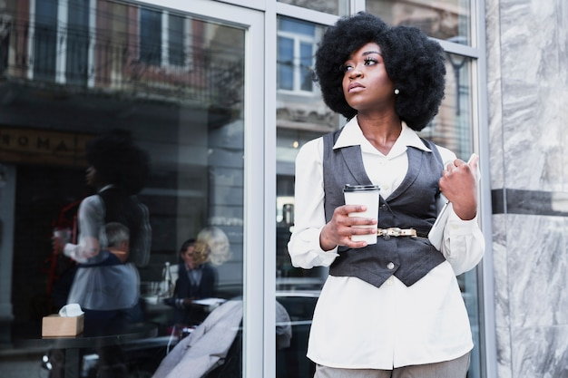 Giovane donna di affari africana alla moda che tiene la tazza di caffè asportabile e distogliere lo sguardo digitale della compressa