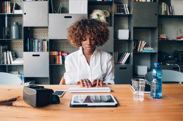 Giovane donna di affari africana che lavora con la compressa in studio moderno