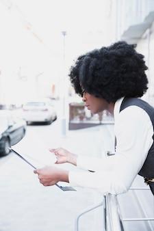 Giovane donna di affari africana che si appoggia sull'inferriata che legge documento su carta