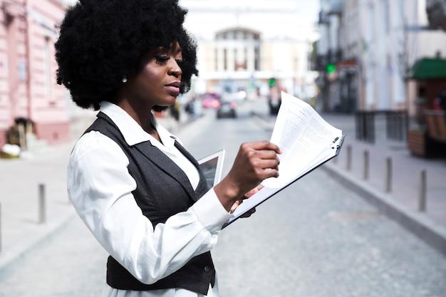 Giovane donna di affari africana che sta sulla strada che legge il documento sulla lavagna per appunti