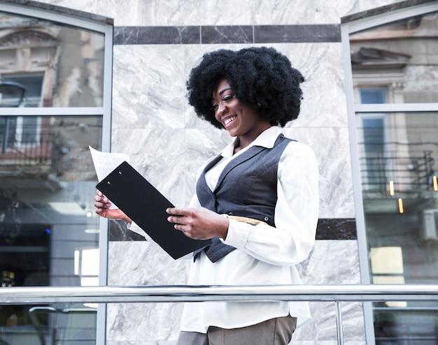 Giovane donna di affari africana giovane sorridente che controlla la carta sulla lavagna per appunti