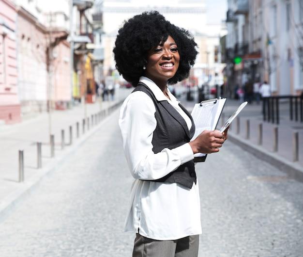 Giovane donna di affari africana sorridente che sta nella lavagna per appunti della tenuta della strada di città che distoglie lo sguardo