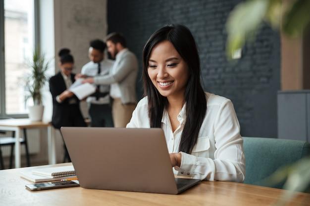 Giovane donna di affari asiatica allegra che per mezzo del computer portatile