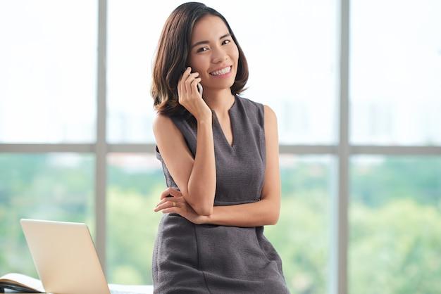 Giovane donna di affari asiatica che chiacchiera sul telefono