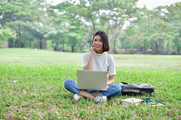 Giovane donna di affari asiatica che lavora nel giardino