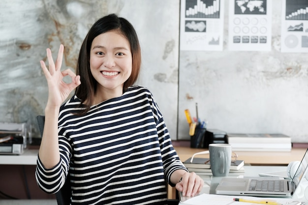 Giovane donna di affari asiatica che mostra gesto di mano giusto