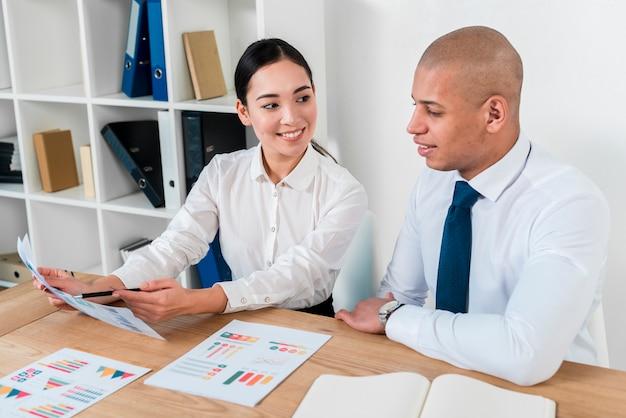 Giovane donna di affari asiatica che mostra rapporto di affari al suo collega