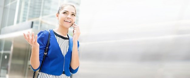 Giovane donna di affari asiatica che parla sullo smartphone con il gesto di mano davanti all'edificio per uffici