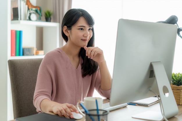 Giovane donna di affari asiatica che per mezzo del lavoro del computer dalla casa