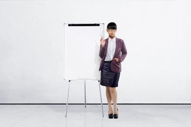 Giovane donna di affari asiatica con la penna di indicatore che sta accanto alla lavagna