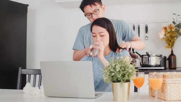 Giovane donna di affari asiatica seria, stress, stanca e malata mentre si lavora al computer portatile a casa. il marito le dà il bicchiere d'acqua mentre lavora sodo nella cucina moderna a casa la mattina.