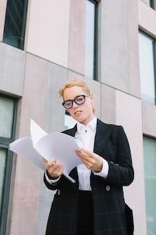 Giovane donna di affari bionda che sta fuori dell'ufficio che esamina i documenti