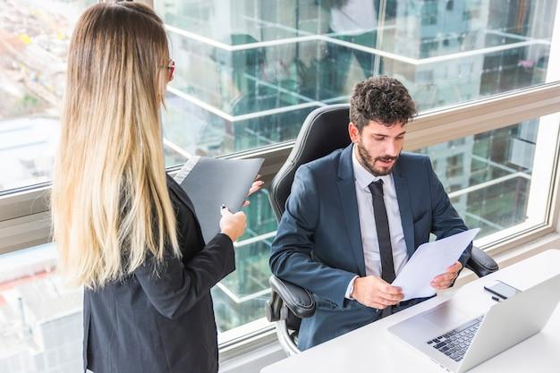 Giovane donna di affari bionda che sta vicino al documento della lettura dell'uomo d'affari