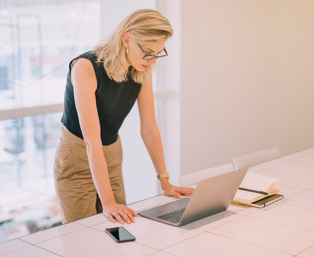 Giovane donna di affari bionda che sta vicino allo scrittorio che esamina computer portatile
