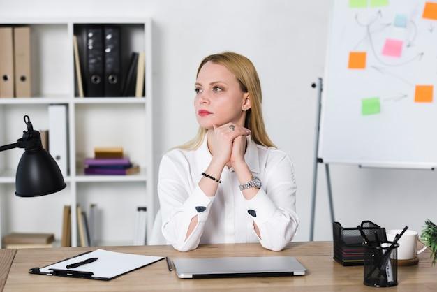 Giovane donna di affari bionda contemplata che si siede nel luogo di lavoro nell'ufficio