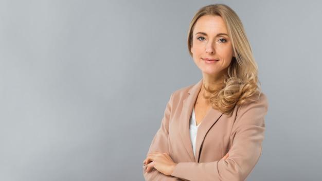 Giovane donna di affari bionda sicura che si leva in piedi contro la priorità bassa grigia