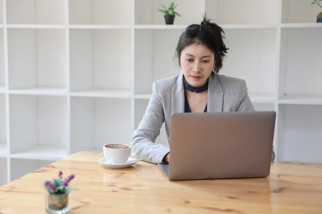 Giovane donna di affari caucasica che lavora al computer portatile con caffè caldo allo scrittorio di legno nel blocco. lavoro da casa.