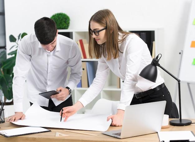 Giovane donna di affari che discute progetto con il suo collega maschio su libro bianco sopra lo scrittorio